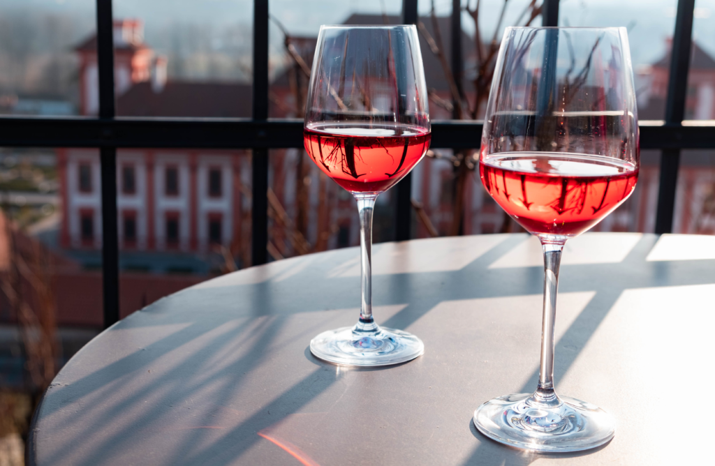 "<img class=""aligncenter lazy"" data-src=""http://www.journeys6senses.com/wp-content/uploads/2020/03/image-17-1024x668.png"" alt=""Розовое вино в бокале"" title=""На фото два бокала с розовым вином на фоне виноградников и замка, Прага"">"